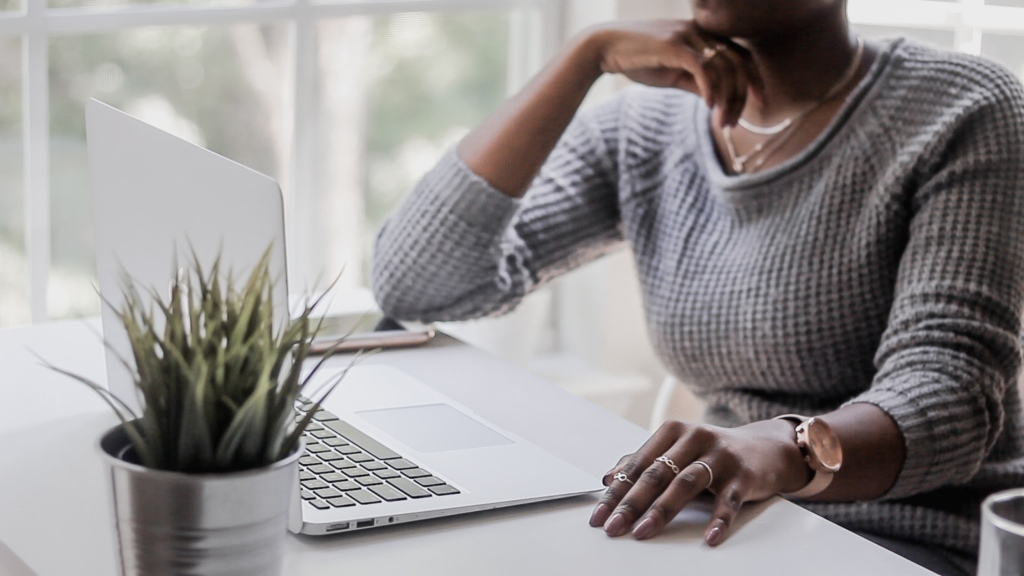A black business woman sitting in front of window wearing a gray sweater hosting a virtual event. This is a way to still do business during social distancing  as a result of coronavirus aka covid-19.